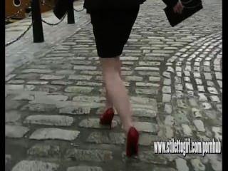走在穿稀薄的紅色短劍的大卵石的性感的高跟的婦女