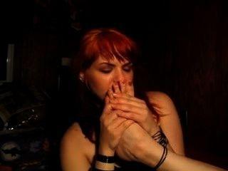 淘氣的紅發女郎嗅著自己臭的腳