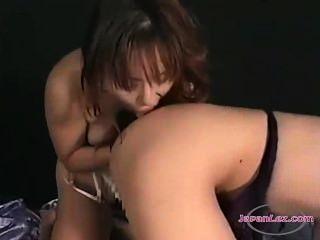 亞洲女孩得到她的乳頭舔舔其他女孩在床上的貓