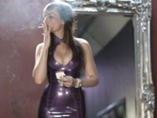 吸煙在紫色乳膠禮服的女孩強的香煙