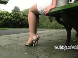 漂亮寶貝炫耀她柔滑光滑的尼龍腿和毫無色的高跟鞋