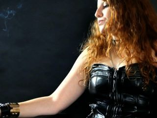 抽煙的紅頭髮人julietta在皮革緊身衣和束腰