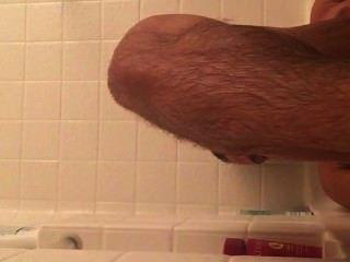 肌肉男孩和他的性感的腳在木盆
