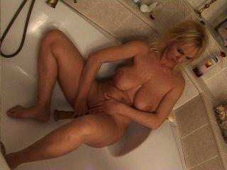 成熟的金發女郎在浴缸裡騎假陽具