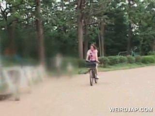 可愛的青少年亞洲辣妹騎自行車得到貓所有濕