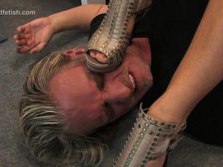 德國女孩坐在她的奴隸和支配他用腳